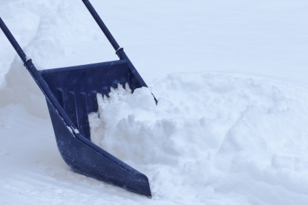 blizzard: Manual snow removal from driveway using a snow scoop after blizzard