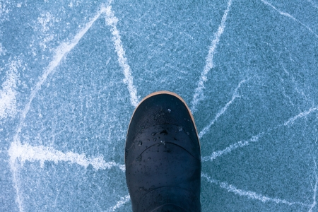 Thin ice cracking under weight of rubber boot human foot walking with cracks radiating outwards signalling high danger