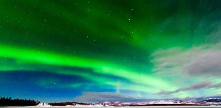 Spectaculaire weergave van intense noorderlicht of Aurora borealis of poollicht vormen groene wervelingen over bevroren Lake Laberge Yukon Territory Canada winterlandschap