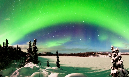 Spectacular display of intense Northern Lights or Aurora borealis or polar lights forming green arc over snowy winter landscape