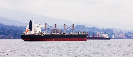 Busy commercial coastal shipping lane with two overseas freighters passing each other close to North Vancouver coastline with urban buildings photo
