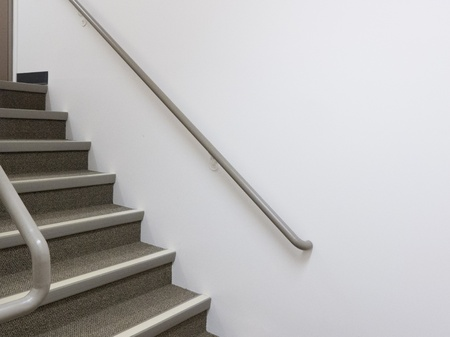 both sides: Flight of stairs in well lit building  with safety banister handrails on both sides Stock Photo