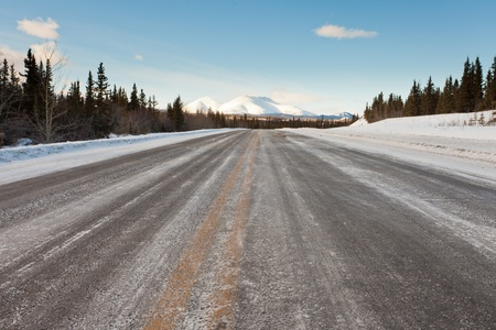 Winter conditions on rural country road in boreal forest taiga leading to beautiful snowcovered distant mountains photo