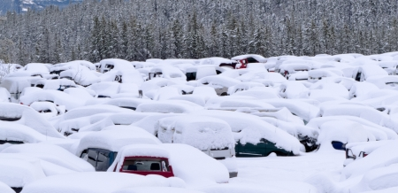 Extreme blizzard weather conditions bring heavy snow that buries hundreds of vehicles in car park or scrap junk yard  photo