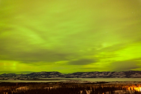 Green glowing display of Northern Lights or Aurora borealis or polar lights in cloudy night sky over taiga forest landscape of Yukon Territory  Canada Stock Photo - 18219003