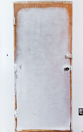 insulate: Ice and hoar frost covered closed wooden door that is not insulated well enough to keep extreme cold out Stock Photo