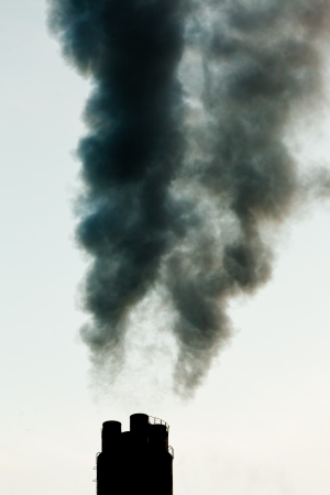Smokestack chimneys belching black smoke  pollutants and greenhouse gas into the atmosphere polluting and contributing to global warming photo