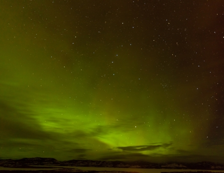 Green glowing display of Northern Lights or Aurora borealis or polar lights in night sky with clouds and stars over taiga forest landscape of Yukon Territory  Canada Stock Photo - 18219027