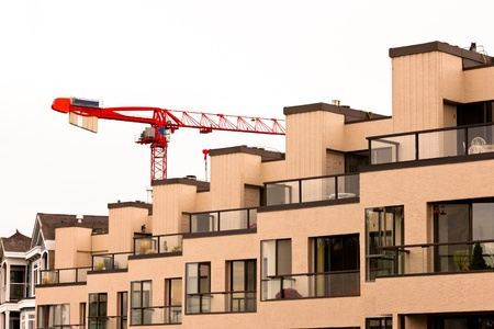 condominium complex: Tower crane over external facade of contemporary residential apartment block development with large glass windows and balconies for every unit