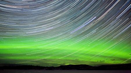 trails of lights: Astrofotografia sentieri stelle con visualizzazione di verde incandescente boreale o aurora boreale nel territorio dello Yukon in Canada