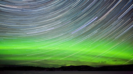 aurora borealis: Astrophotography star trails with green glowing display of Northern Lights or Aurora borealis in Yukon Territory  Canada Stock Photo