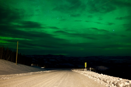 Northern Lights or Aurora borealis or polar lights illuminating overcast sky over snowy winter road landscape Stock Photo - 18219049