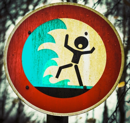 Grungy warning sign for flash flood  flooding  big tidal waves or tsunami with a pictorial signboard showing a person shouting out in panic about to be engulfed by high water photo