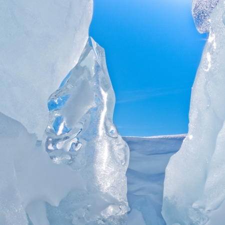 Narrow icy crevasse of glacier with some fresh snow and blue sunny sky visible in the opening Stock Photo