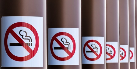 Series of No Smoking signs mounted on columns with diminishing perspective for a healthy smoke free environment