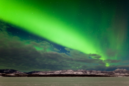 Spectacular display of intense Northern Lights or Aurora borealis or polar lights forming a green band over snowy winter landscape of Lake Laberge  Yukon Territory  Canada photo