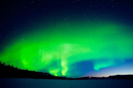 aurora borealis: Spectacular display of intense Northern Lights or Aurora borealis forming green swirls over single isolated illuminated house in vast snowy winter landscape of Lake Laberge  Yukon Territory  Canada Stock Photo