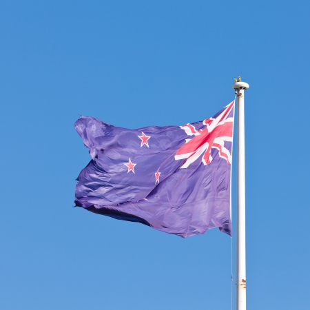 New Zealand national flag banner flying on pole in wind with blue sky background photo