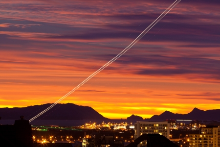 light trail: Sunset and light trail of starting airplane over Manukau  southern suburb of Auckland  New Zealand Stock Photo