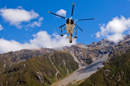 helicopter: Small helicopter hovering mid-air in blue sky over mountains of Southern Alps  New Zealand