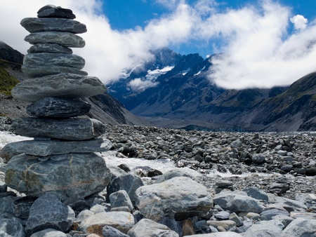 Rock cairn in Hooker Valley on a trail leading to Aoraki  Mount Cook  highest peak of Southern Alps  an icon of New Zealand partially covered in clouds photo