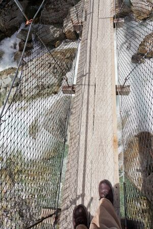 defile: Booted feet of man walking on narrow swing bridge over clear fresh white water rushing through a rocky gorge