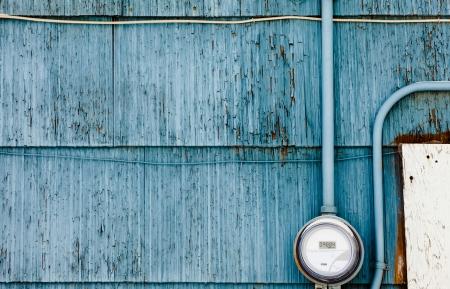 汚れた青の木造外壁にマウントされている現代スマート グリッド住宅デジタル電源メーター