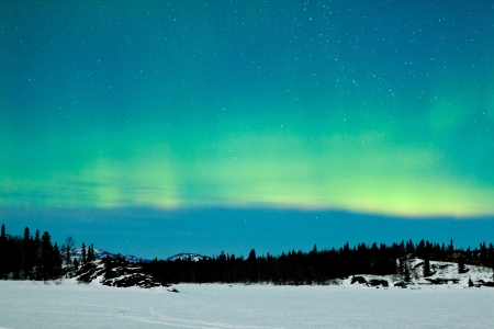 aurora polaris: Spectacular display of intense green Northern Lights or Aurora borealis or polar lights over snowy northern winter landscape