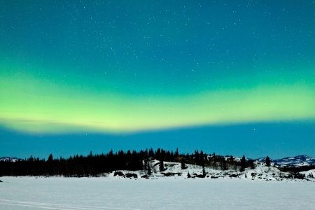 Spectacular display of intense green Northern Lights or Aurora borealis or polar lights over snowy northern winter landscape