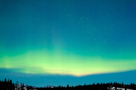 Spectacular display of intense green Northern Lights or Aurora borealis or polar lights over snowy northern winter landscape photo