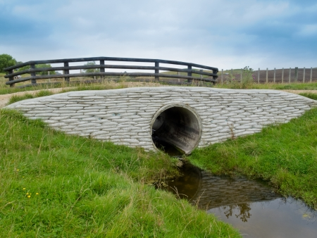 Large circular storm water culvert or drainage pipe passing under a scenic rural road with a rustic wooden fence above and concrete bank reinforcement and water below
