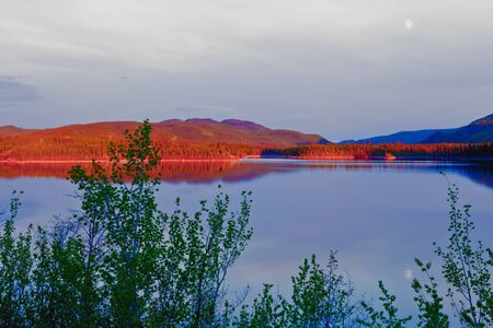 yukon: Red glow of evening sun on boreal forest taiga surrounding calm water surface of Lake  Twin Lake near Carmacks  Yukon Territory  Canada Stock Photo