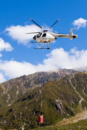 Small helicopter with transport cargo bucket flying in blue sky over mountains of Southern Alps  New Zealand  to supply remote site