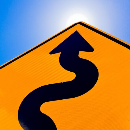 winding: Wavy arrow on road sign pointing upward into a cloudy blue sky in a concept of achievement, advancement and success