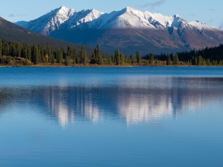 Snowcapped mountain reflection on calm surface of Lapie Lake  Yukon Territory  Canada photo