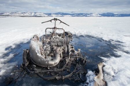 Charred remains of snowmobile burnt out in a winter motorsports mishap on frozen Lake Laberge  Yukon Territory  Canada photo