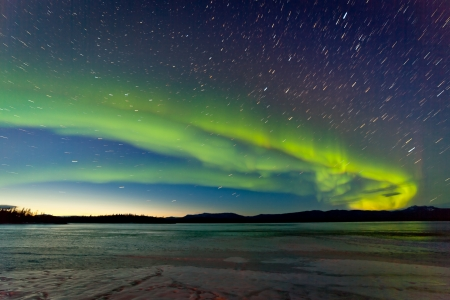 northern: Intense Northern Lights or Aurora borealis or polar lights and morning dawn on night sky over icy landscape of frozen Lake Laberge Yukon Territory Canada