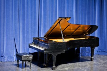 Open gezwart grand piano en pianokruk staande voor blauwe fluwelen gordijnen op het podium klaar voor een muzikale overweging of de prestaties