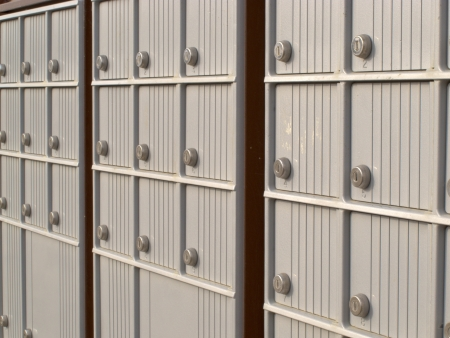 Rows of receding lockers with metal doors and locks of outdoor silver canadian mailboxes for safe delivery of rural mail post 免版税图像 - 19939809