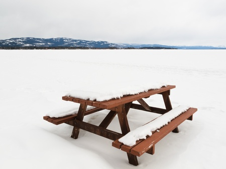 Closed for the season  beautiful lakeside campsite with wooden table and benches burried in snow and wide open flat of snowy frozen lake landscape with pristine white snow on a cold winters day photo