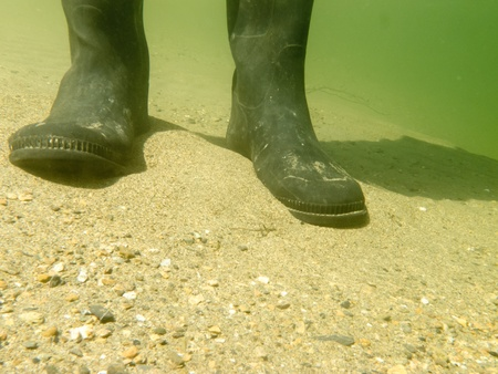 Closeup underwater view of rubber boots gumboots or waders of a person walking in shallow water of gravel and sand beach Banco de Imagens
