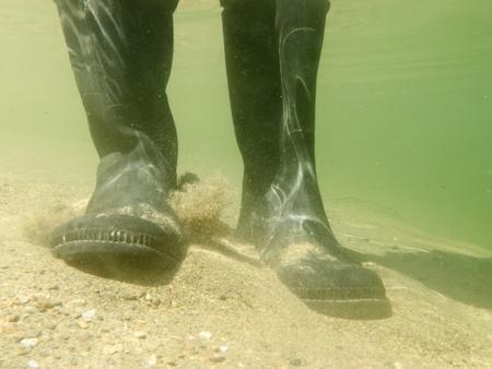 waders: Primer bajo la vista de goma botas botas de goma o botas altas de una persona caminando en aguas poco profundas de guijarros y arena