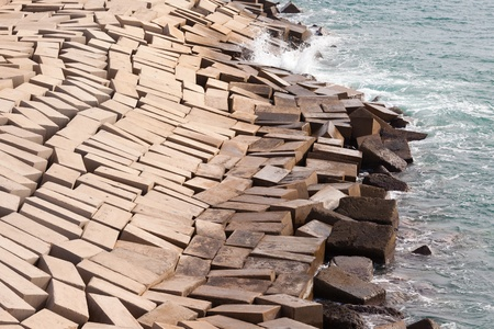 recedes: Concrete blocks laid haphazardly forming a protective coastal seawall to prevent erosion from tides and waves as an architectural abstract Stock Photo