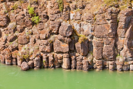 geologic: Close-up of weathered geologic basalt rock cliff wall of Miles Canyon with water of Yukon River  Yukon Territory  Canada