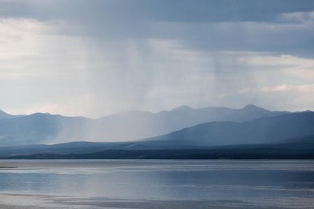 squall: Heavy rain shower over Marsh Lake Yukon Territory Canada and distant mountain range Stock Photo