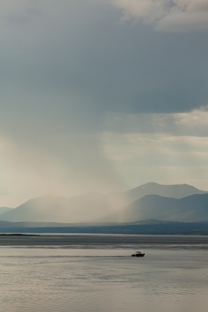 squall: Heavy rain shower over Marsh Lake Yukon Territory Canada and distant mountain range with a small motorboat out on tranquil water