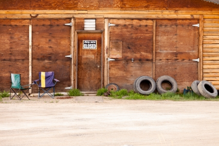 Wooden gate of rural timber building with closed sign and abandoned with two vacant chairs and old tires leaning against outside wall photo