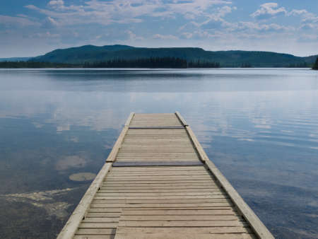 natural  moody: Empty wood plank dock or jetty into dramatic sky reflection on calm still water of Twin Lakes  Yukon Territory  Canada
