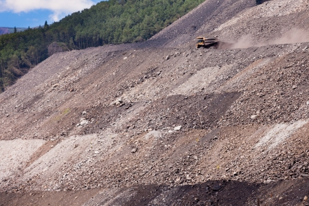 haul: Big mining truck on haul road throwing up dust off its rough surface at steep mountain side with tailings Stock Photo