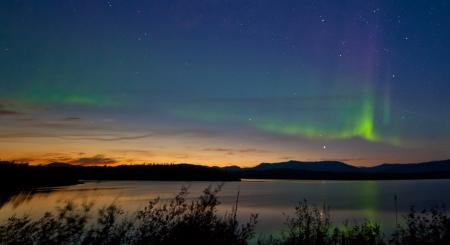 Nordlicht Aurora borealis um Mitternacht im Sommer über dem nördlichen Horizont des Lake Laberge Yukon Territory Kanada am frühen Morgen